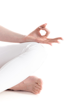 Close up of hands of beautiful sporty young woman sitting cross legged in Easy (Decent, Pleasant Pose), fingers in Jnana mudra, studio full length isolated shot, three-quarters view Stock Photo - 42896250
