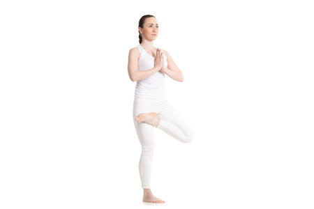 padma: Sporty attractive young woman in white sportswear doing Ardha Padma vrksasana pose, hands in Namaste, leg in half lotus position, isolated, full length three-quarters view