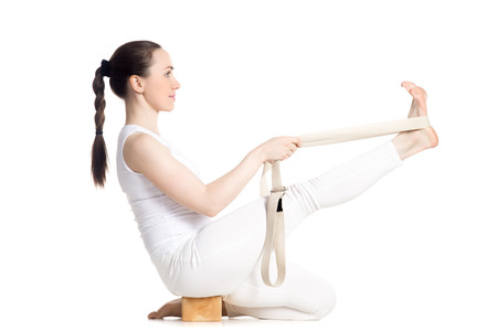 Sporty beautiful young beginning yoga student in white sportswear doing exercises for legs using props: block and strap, sitting in Heron Pose, studio full length isolated shot, side view Reklamní fotografie