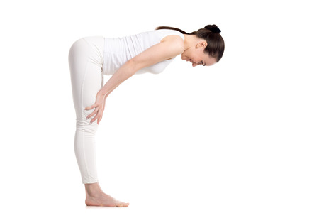 Sporty young beautiful smiling beginning yoga female student in white sportswear doing easy variation of Standing Half Forward Bend, Ardha Uttanasana pose, studio full length shot, isolated