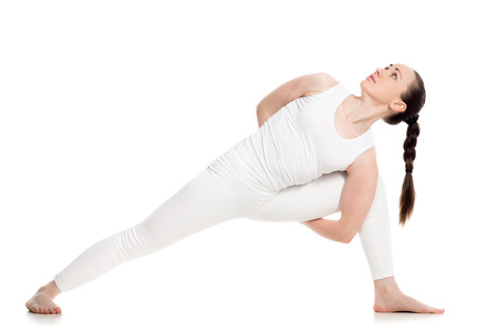 utthita: Sporty attractive young woman in white sportswear doing lunge exercise for spine, variation of utthita parshvakonasana with hands behind back, part of large photo series, isolated, full length