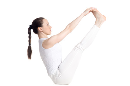 big toe: Sporty beautiful young woman in white sportswear doing exercises for legs and abs, sitting in Ubhaya Padangusthasana asana, Both Big Toe pose, studio full length isolated shot, side view