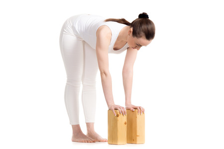 ardha: Sporty beautiful young woman in white sportswear doing variation of Ardha Uttanasana pose with wooden blocks, studio full length three-quarters view on white background, isolated Stock Photo