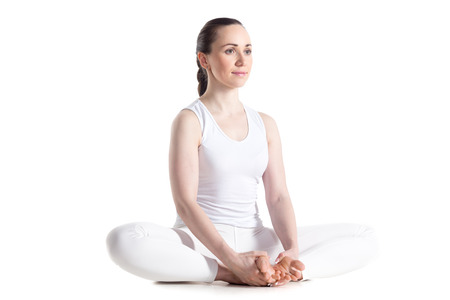 baddha: Sporty beautiful smiling young woman in white sportswear sitting in baddha konasana, bound angle, cobbler, butterfly pose, studio full length isolated shot, three-quarters view Stock Photo