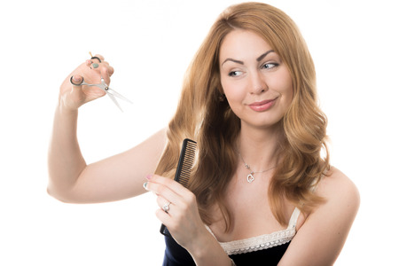 Funny portrait on white background of young attractive smiling blond Caucasian beautician woman holding hairdresser scissors and hair comb before cutting her hair, studio shot