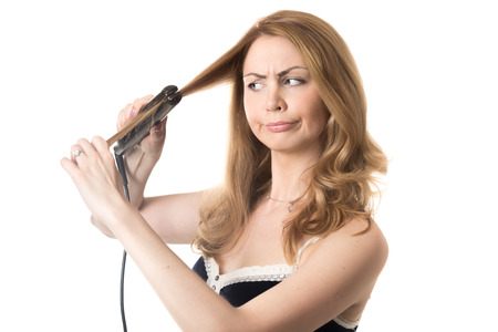 bad mood: Funny frowning young attractive blond woman holding hair straightener, in bad mood because of her hairstyle, studio isolated portrait on white background