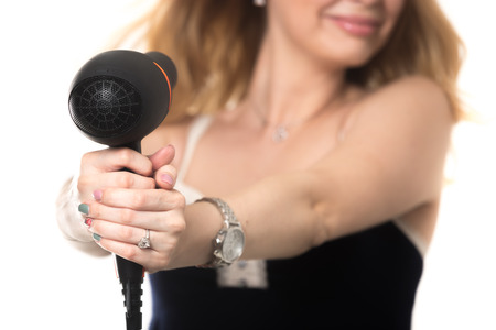 sexy hands: Young attractive blond woman drying her hair, holding black hairdryer on stretched arms pointing at her face, fooling around, close up, focus on dryer, studio shot, isolated on white background Stock Photo