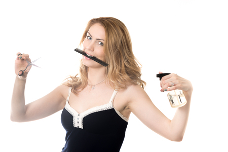 eager: Funny portrait of young smiling attractive blond beautician woman holding comb in her mouth, hairdresser scissors and spray bottle in her arms, ready to do hairstyle, studio on white background