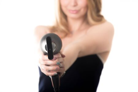 capelli biondi: Young funny attractive blond Caucasian woman fooling around, holding black hair dryer like gun aiming towards camera, close up, focus on dryer, studio shot, isolated on white background