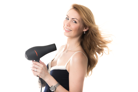 hot chick: Portrait of young happy smiling gorgeous blond Caucasian woman model drying her long hair using black electric hairdryer, studio shot, isolated on white background Stock Photo