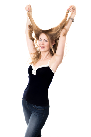 messing: Funny portrait of young attractive cheerful smiling blond Caucasian woman fooling around, having fun messing her long hair with happy expression, studio shot on white background
