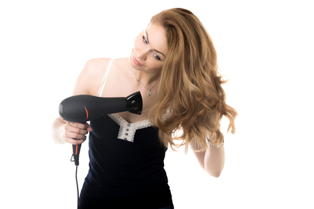 capelli biondi: Portrait of young gorgeous blond Caucasian woman using black hair dryer, drying her beautiful long hair with happy smile, studio shot, isolated on white background