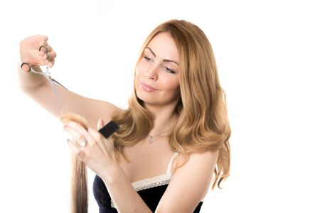 hairdressing scissors: Portrait of young attractive smiling blond beautician Caucasian woman working, holding strand of hair, doing haircut using hairdressing scissors and comb, studio shot on white background