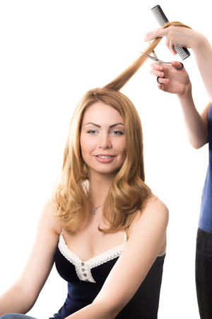 hair studio: Portrait of young smiling attractive blond woman sitting at beauty salon having her long hair cut, studio shot, isolated on white background