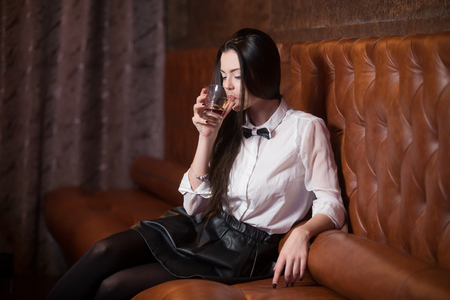 glamour woman elegant: Beautiful brunette girl in white shirt and black bow tie at restaurant, holding glass with drink at party, drinking alcohol
