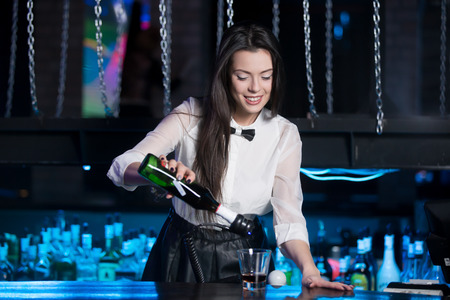 vip beautiful: Beautiful cheerful brunette bartender girl in white shirt and black bow tie, serving alcohol drink at nightclub bar, holding bottle in hand, pouring drink in glass