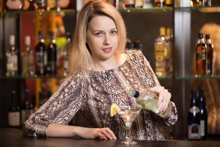 Glimlachend blonde vrouwelijke bartender op het werk, die fles in de hand, kijkend naar de camera tijdens het gieten drank in martini glas Stockfoto