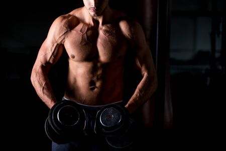 brawny: Young attractive caucasian bodybuilder sportsman working out with dumbbells in gym, doing training for shoulder muscles, close up