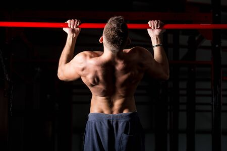 strong chin: Young attractive caucasian crossfit sportsman working out in gym, exercising on chin-up bar, doing pull-ups for arms and back muscles, rear view Stock Photo