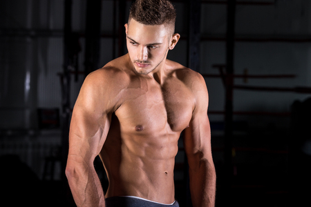 tense: Portrait of young attractive caucasian athletic bodybuilder man working out in sports center, posing, showing abdominal and arm muscles, body sculpture concept