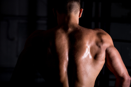nude back: Rear view of young attractive caucasian muscular bodybuilder man with perfect body working out in sports center, posing, showing back muscles, body sculpture concept