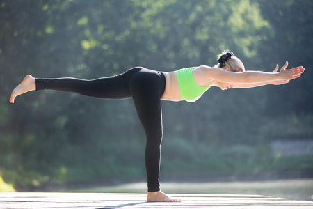 balance: Beautiful sporty fit blond young woman in green sportswear working out outdoors, standing in Warrior III posture (Virabhadrasana 3), Balancing Stick Pose (Tuladandasana), full length