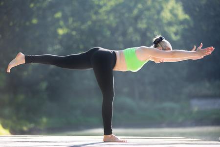 balanza: Hermosa mujer joven deportiva ajuste rubia en ropa deportiva verde ejercicio al aire libre, de pie en la postura Warrior III (Virabhadrasana 3), Equilibrio de la postura del palo (Tuladandasana), de cuerpo entero Foto de archivo