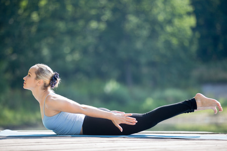 asana: Beautiful sporty fit young woman in sportswear working out outdoors in park on summer day, doing Salabhasana, Locust Posture, Double Leg Kicks exercise, backward extension of the spine, full length Stock Photo