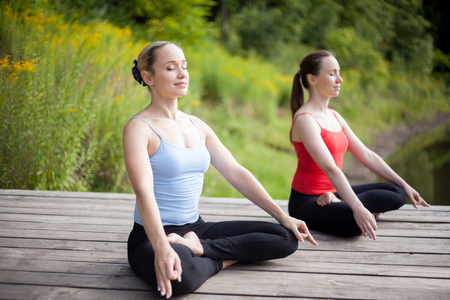 cross legged: Two serene young beautiful women on meditation session outdoors, sitting cross-legged in Ardha Padmasana Posture, working out in park on summer day, practicing pranayama with closed eyes, full length Stock Photo