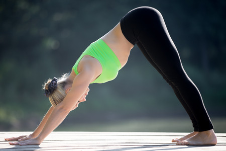 namaskar: Beautiful sporty blond young woman working out outdoors on wooden deck, standing in downward facing dog posture, surya namaskar complex, full length