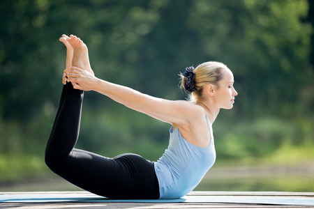 Mooie sportieve fit blonde jonge vrouw gekleed in een blauwe tank top sportkleding uit te werken buitenshuis op zomerse dag, doen basishouding Dhanurasana, Bow Pose, volledige lengte
