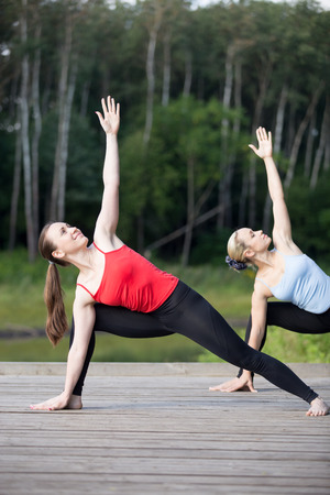 parsvakonasana: Two happy smiling young beautiful women working out in park on summer day, wearing sportswear red and blue tank tops, standing in Utthita Parsvakonasana (Extended Side Angle posture), full length Stock Photo