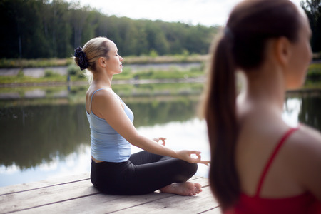 sukhasana: Two serene beautiful sporty fit young women working out on the lake on summer day, Sitting in Easy (Pleasant Posture), Sukhasana, meditating with closed eyes, breathing, back view