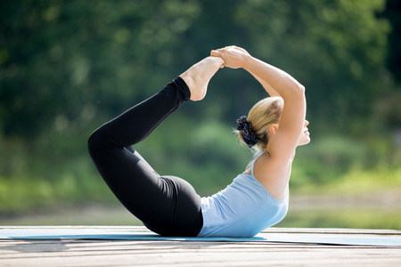 dhanurasana: Beautiful sporty fit blond young woman wearing blue tank top sportswear working out outdoors on summer day, doing deep back bending exercises, Padangustha Dhanurasana, Big Toe Bow Posture Stock Photo