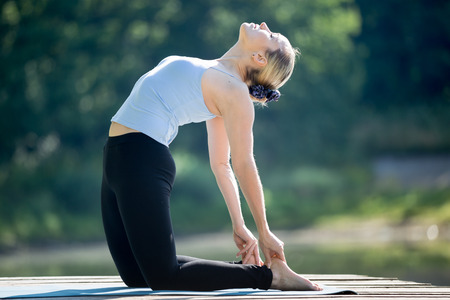 ushtrasana: Beautiful sporty fit blond young woman in blue tank top sportswear working out outdoors in park on summer day, doing ushtrasana, Camel Posture, full length Stock Photo