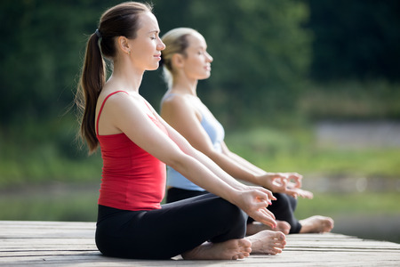 sukhasana: Two beautiful sporty fit young women sitting in Easy (Pleasant Posture), Sukhasana, meditating with closed eyes, breathing, working out outdoors in summer, wearing red and blue tank tops sportswear Stock Photo