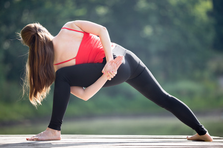 hands behind back: Fit young beautiful woman wearing red tank top and black sporty leggings working out outdoors in park on summer day, doing parivritta parshvakonasana variation with hands behind back, rear view