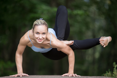 parivrtta: Happy smiling fit young beautiful woman practicing yoga outdoors in park on summer day, doing arm balance, Dragonfly yoga posture, Maksikanagasana, Parivrtta Eka Pada Danda Koundiniasana, full length