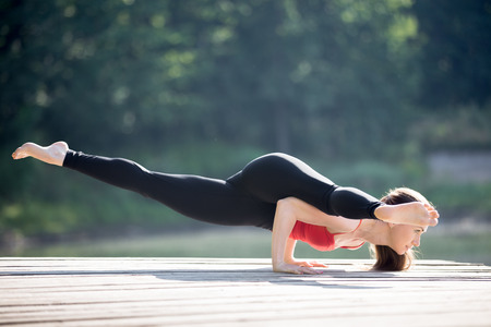 leg: Fit young beautiful woman wearing red tank top and black sporty leggings working out outdoors in park on summer day, doing Eka Pada Koundinyasana 2, twisted one legged arm balance Stock Photo