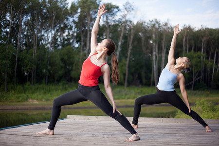 virabhadrasana: Two fit young beautiful women doing Reverse Warrior Pose, Crescent lunge variation, Viparita Virabhadrasana, working out in park on summer day, wearing sportswear red and blue tank tops, full length Stock Photo