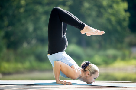 formidable: Beautiful sporty fit blond young woman in sportswear working out outdoors in park on summer day, doing Ganda Bherundasana, Formidable Face Posture, full length