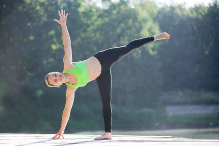moon: Beautiful smiling sporty fit blond young woman in green sportswear working out outdoors on wooden pontoon on the lake, standing in ardha chandrasana, half moon posture, full length Stock Photo