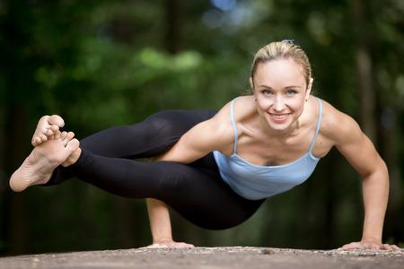Happy lachende fit jonge mooie vrouw het beoefenen van yoga buiten in park op zomerse dag, het doen van asymmetrische arm evenwichtsoefening, asana Astavakrasana, Acht-Angle Houding, full length Stockfoto