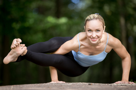 muscle girl: Happy smiling fit young beautiful woman practicing yoga outdoors in park on summer day, doing asymmetrical arm balancing exercise, asana Astavakrasana, Eight-Angle Posture, full length Stock Photo