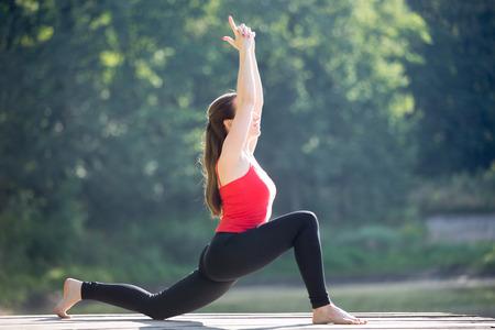 haciendo ejercicio: Ajuste a la mujer joven y bonita que desgasta la tapa del tanque rojo y leggings deportivo negro que se resuelve en el parque el día de verano, hacer ejercicio de bajo estocada, Anjaneyasana, la postura Sanchalanasana Ashwa, de cuerpo entero