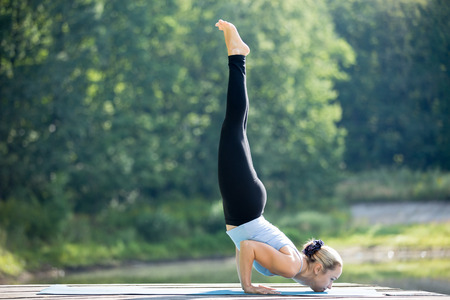 formidable: Beautiful sporty fit blond young woman in sportswear working out outdoors in park on summer day, doing variation of Ganda Bherundasana, Formidable Face Posture, full length