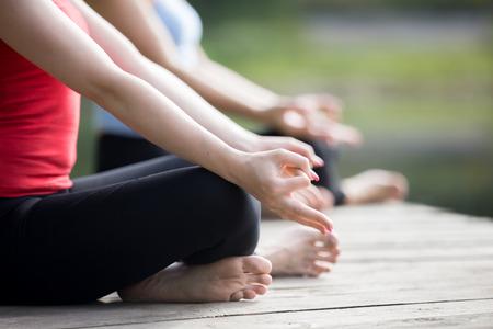 2 美しいスポーティなフィット若い女性の瞑想や屋外呼吸、簡単 (快適な姿勢)、Sukhasana、夏の日のワークアウト スポーツウェアを着て座っている手