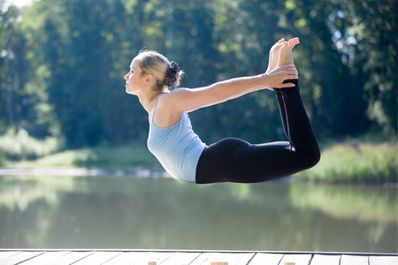 dhanurasana: Serene young sporty beautiful woman floating in midair during yoga practice, levitating above ground in Dhanurasana posture, Bow Pose, working out outdoors in summer park, full length