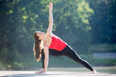 parsvakonasana: Beautiful sporty fit young woman in sportswear working out outdoors on summer day, standing in Utthita Parsvakonasana, Extended Side Angle Posture, full length Stock Photo