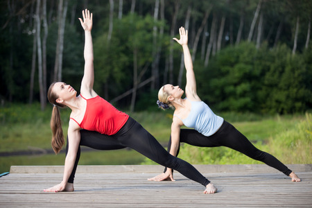 utthita: Two fit young beautiful women doing utthita parshvakonasana (Extended Side Angle posture), working out outdoors in park on summer day, wearing sportswear red and blue tank tops, full length